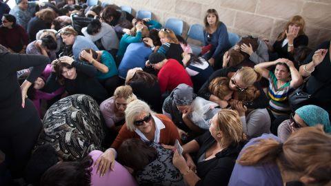 People take cover during a rocket attack at a funeral Friday, November 16, in Kiryat Malakhi, Israel.