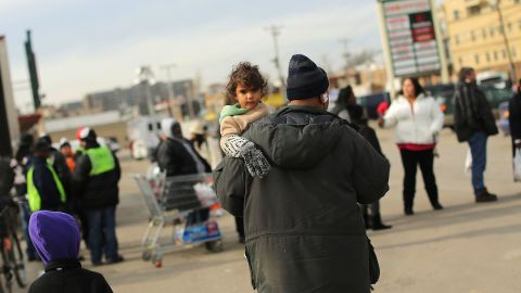 Residents wait for free food in a parking lot in Rockaway on Friday.