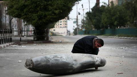 A Palestinian Hamas policeman looks at an Israeli rocket in the street in Gaza City on Saturday, November 17.