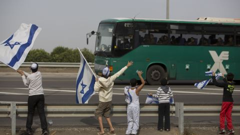 Israeli children wave their national flag Saturday, November 17, as they greet a bus carrying soldiers on a road leading to the Israel-Gaza border near the southern Israeli town of Ofakim.
