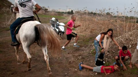 Israeli civilians run for cover during a rocket attack launched from Gaza on November 17 in Tel Aviv, Israel.