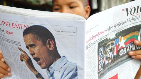 A Buddhist Monk reads a local newspaper carrying a picture of U.S. President Obama in downtown Yangon on Saturday.