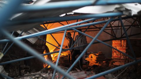 Palestinians walk amid the debris of a burning factory near the house of Ezzedine Haddad, commander of the armed wing of the Hamas movement, after it was destroyed during an Israeli air strike on Gaza City on Saturday, November 17.