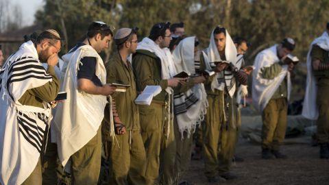 Israeli soldiers wearing prayer shawls conduct morning prayers Sunday, November 18, at an Israeli army deployment area.