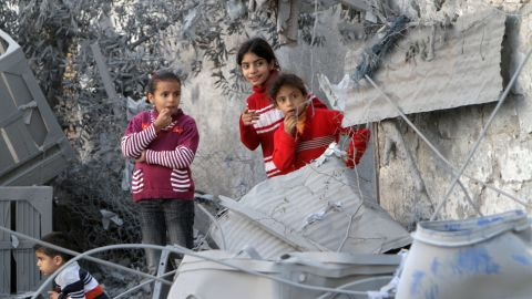 Palestinian children look at damaged buildings following Israeli air strikes Sunday, November 18, in Rafah.