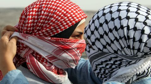 A Palestinian woman helps her friend cover her face with a traditional scarf during clashes at the Hawara checkpoint in the occupied West Bank city of Nablus on Saturday, November 17. People rallied against the Israeli military operations.