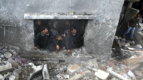 Palestinians search the debris of the home following an Israeli airstrike in Gaza City on Sunday, November 18.