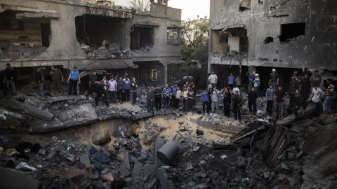 Palestinian men gather around a crater caused by an Israeli airstrike at a home in Gaza City on Sunday, November 18.