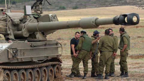 Israeli soldiers prepare an artillery emplacement overlooking Gaza .