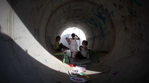 Israeli children play in a large concrete pipe used as a bomb shelter on Monday in Nitzan.