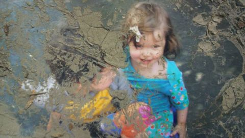 Two colorfully dressed children play in this photograph, caked with mud after Superstorm Sandy.