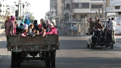 Palestinian families evacuate their homes following an Israeli airstrike Tuesday in Gaza City.  More than 100 Palestinians have been killed in the weeklong attacks, the Gaza Ministry of Health says. Four Israelis have died.
