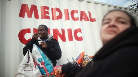 Wilma Marrero and son Joseph Kendall wait in line about five hours Tuesday for food and other items from a Coney Island distribution point in Brooklyn, New York.