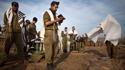 Israeli soldiers pray next to an artillery gun along Israel's border with Gaza on Wednesday, November 21. Violence continued in the region Wednesday, leaving hopes of a cease-fire in tatters just hours after a halt in fighting seemed close.