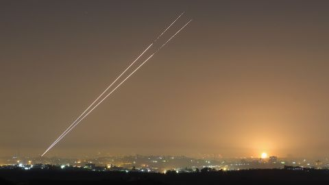 Rockets launch from Gaza City as an explosion is seen on the horizon at Israel's border with Gaza on Wednesday.