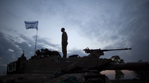 An Israeli soldier stands on his tank in a deployment area on November 22, 2012 on Israel's border with the Gaza Strip.