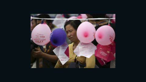 A woman looks at notes hung on balloons by single men and women who hope to meet members of the opposite sex in Chongqing, China on Singles Day.