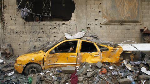 A Palestinian boy plays in a demolished car in Gaza City on Friday.