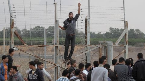 Palestinian youths gesture during a demonstration next to the security fence on the Gaza border with Israel east of Khan Yunis, in the southern Gaza Strip, on Friday, November 23. A Palestinian was shot dead by Israeli forces near the Gaza border, the first casualty since the two sides agreed a truce ending their week-long conflict, Palestinian medical sources said.