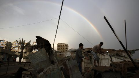 Palestinians inpect the rubble of a destroyed house as a rainbow arcs over Gaza City on November 23, 2012.