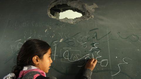 A Palestinian schoolgirl writes on the blackboard of a classroom in Gaza City on Saturday.