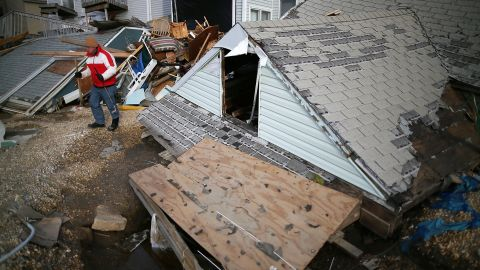 """David McCue stands near the roof of his beach house, which was completely demolished by Superstorm Sandy, in Ortley Beach, New Jersey, on Sunday, November 25. <a href=""""http://www.cnn.com/2012/10/30/us/gallery/sandy-damage/index.html"""" target=""""_blank""""><strong>See photos of the immediate aftermath of Sandy.</strong></a>"""