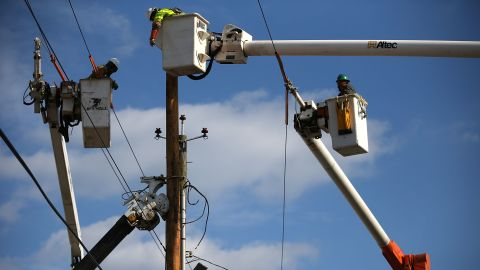 Utility workers replace a pole Sunday that was damaged by Superstorm Sandy in Seaside Heights, New Jersey.