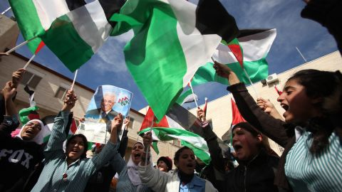 Palestinian students wave their flag in the West Bank city of Ramallah, on November 25, 2012