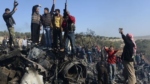 Syrian rebels celebrate on top of the remains of a Syrian government fighter jet which was shot down at Daret Ezza, on November 28, 2012.