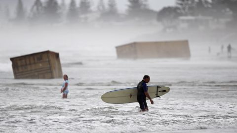 <strong>January 10: </strong>A surfer walks past cargo containers washed ashore from the stricken container ship Rena at Waihi Beach in New Zealand. The ship was stranded on a reef for more than three months before breaking up and sinking in rough seas, littering beaches with cargo and debris.