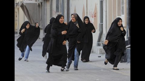 """<strong>June 27: </strong>Protesters run for cover as police arrive to disperse a rally demanding human rights reforms in the village of Buri, south of Bahrain's capital, Manama. A court in Bahrain sentenced prominent activist Nabeel Rajab to three years in prison in August """"for participating in illegal rallies and gatherings."""""""