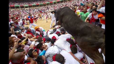 <strong>July 8:</strong> A wild bull hurdles over people blocking the animal's way into the bullring at the close of the second bull run during the Fiesta de San Fermin in Pamplona, Spain. The festival attracts thousands of people who attempt to outrun the bulls through the narrow streets of the old city.
