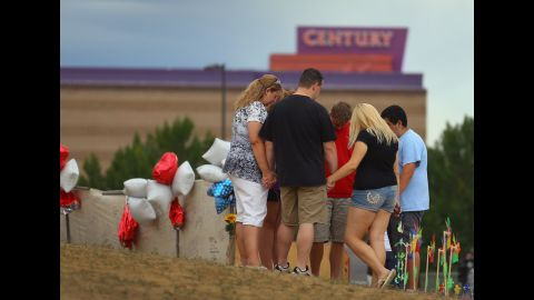 """<strong>July 28:</strong> Visitors gather and pray around a cross erected at a memorial set up across the street from the Century 16 movie theater in Aurora, Colorado. James Holmes is suspected of killing 12 people and injuring 58 others during a shooting rampage on July 20 at a screening of """"The Dark Knight Rises."""""""