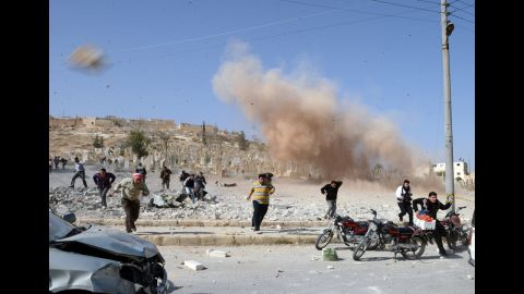 <strong>November 4:</strong> Syrians take cover as a second bomb explodes during a rescue attempt in a nearby building that was hit during an air raid by government forces in the northern city of Al-Bab.
