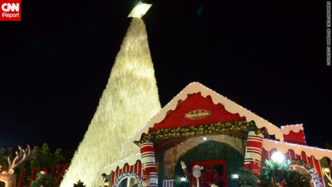 """In the Philippines, Christmas trees come <a href=""""http://ireport.cnn.com/docs/DOC-887845"""">in all shapes and sizes</a> -- this one in iReporter Miaflor Tatlonghari's image is at least 30ft tall and towers over Santa Claus's house in Santa Rosa city."""