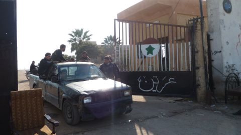 Syrian rebel fighters drive through the gate of the Syrian Government army Base 46 after its capture, near Aleppo, on November 21, 2012
