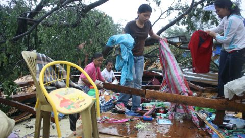 Residents gather their belongings after their house was destroyed by strong winds brought about by Typhoon Bophal in Cagayan de Oro City, southern island of Mindanao on December 4, 2012. Typhoon Bopha smashed into the southern Philippines early December 4, as more than 40,000 people crammed into shelters to escape the onslaught of the strongest cyclone to hit the country this year. AFP PHOTO (Photo credit should read STR/AFP/Getty Images)