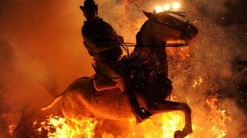 <strong>January 16:</strong> A man rides a horse through a bonfire in the small village of San Bartolome de Pinares, Spain, in honor of San Anton, the patron saint of animals.