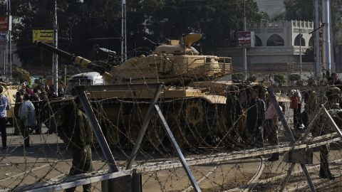 Egyptian army soldiers set up barbed wire barricades and deploy tanks outside of the Egyptian presidential palace in Cairo on December 6, 2012.