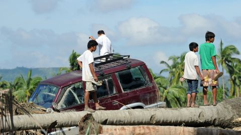 Residents stand next to a vehicle washed up among debris along a river in New Bataan on December 6.