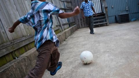 A Bangladeshi boy plays soccer with his father in Baltimore, Maryland.