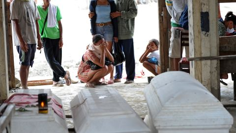 Residents in New Bataan mourn near coffins of relatives who died during flash floods caused by Typhoon Bopha on Saturday, December 8.