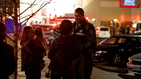 A law enforcement officer talks to people waiting outside the mall.