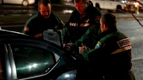 Lt. James Rhodes of the Clackamas County Sheriff's Office works with other responders in the parking lot of the mall.