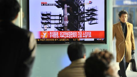 Travellers watch a TV screen broadcasting news on North Korea's rocket launch, at a railway station in Seoul on December 12, 2012.