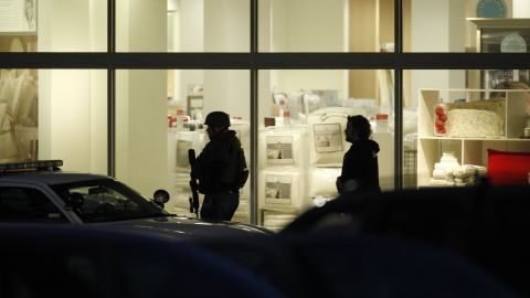 Two people walk in front of the lit windows of the mall on Tuesday night.