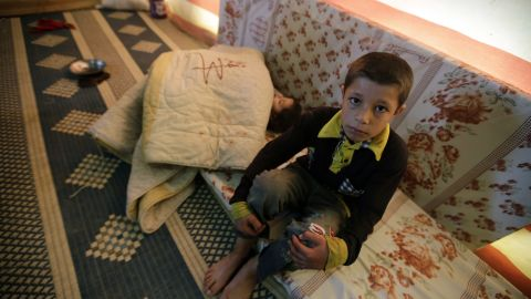 A Syrian refugee child sits near his sleeping sister at his family's makeshift house built on an agricultural field in Saadnayel in the Lebanese Bekaa valley on December 12, 2012.
