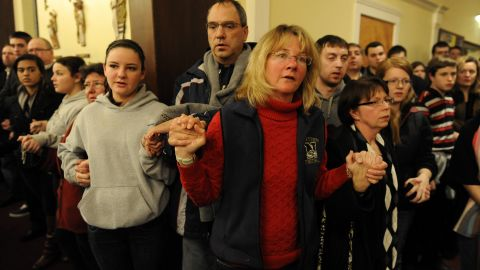 People gather inside the St. Rose Church to remember the shooting victims on Friday