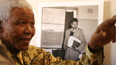Mandela shows something to a group of international journalists visiting the Nelson Mandela Foundation in Johannesburg in May 2004.