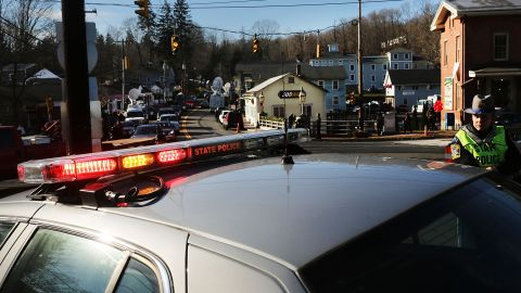 Police officers keep guard at the entrance to the street leading to the Sandy Hook Elementary School on Saturday, December 15.